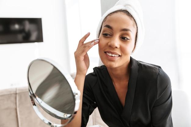 Retrato de uma jovem afro-americana em um roupão, enrolada em uma toalha branca, aplicando creme facial contra o espelho