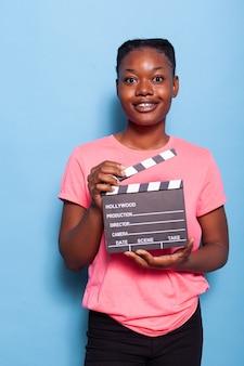 Retrato de uma jovem afro-americana sorridente segurando uma ripa de filmografia