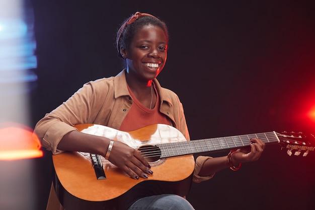 Retrato de uma jovem afro-americana tocando guitarra no palco e sorrindo, copie o espaço da cintura para cima