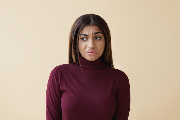 Retrato de uma jovem afro-americana triste e insatisfeita, tendo expressão ofendida após brigar com o marido. moda feminina mestiça se sentindo descontente, enojada com o mau cheiro ou fedor