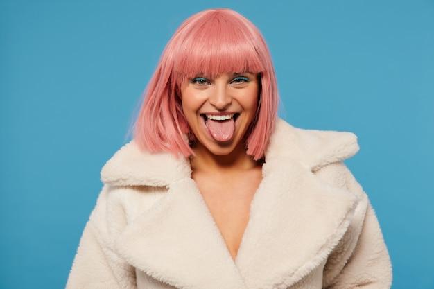 Retrato de uma jovem alegre adorável mulher de cabelo rosa com corte de cabelo curto, olhando alegremente e mostrando a língua, vestida com um casaco de pele sintética branco