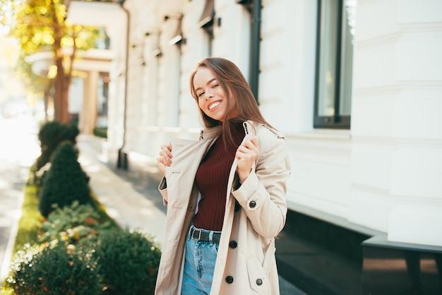 Retrato de uma jovem alegre ao ar livre na rua na cidade ao pôr do sol