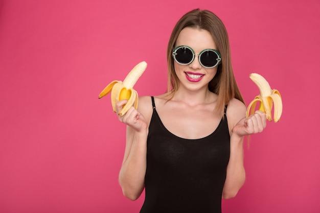 Retrato de uma jovem alegre, atraente e positiva em óculos de sol pretos, segurando duas bananas na parede rosa