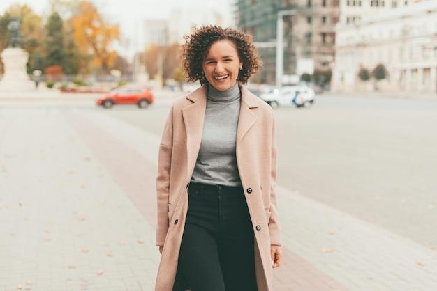 Retrato de uma jovem alegre com cabelo encaracolado, vestindo um casaco bonito, andando na rua