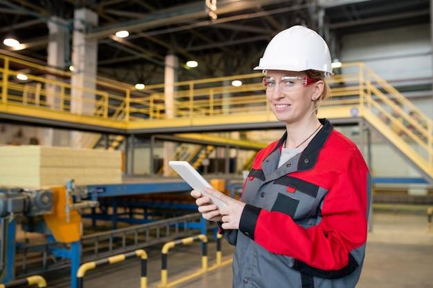 Retrato de uma jovem alegre com óculos de proteção e capacete de segurança, verificando os dados do tablet na fábrica de construção