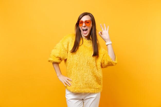 Retrato de uma jovem alegre com suéter de pele, calça branca e óculos coração laranja mostrando sinal de ok isolado no fundo amarelo brilhante. emoções sinceras de pessoas, conceito de estilo de vida. área de publicidade.