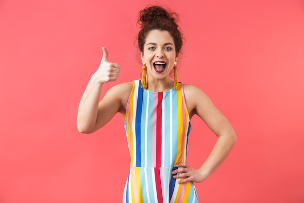 Retrato de uma jovem alegre com um vestido de pé isolado sobre um fundo vermelho, polegar para cima