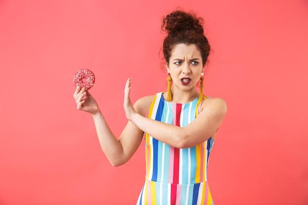 Retrato de uma jovem alegre com um vestido de pé isolado sobre um fundo vermelho, posando, segurando donuts