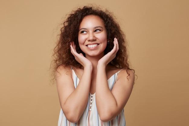 Retrato de uma jovem alegre de cabelos castanhos cacheados com maquiagem natural, mantendo as palmas das mãos levantadas sob o queixo e olhando alegremente de lado, isolado no bege