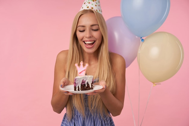 Retrato de uma jovem alegre, de cabelos compridos, com vestido azul de verão, comemorando o feriado, posando em balões de ar multicoloridos com bolo de aniversário, isolado sobre um fundo rosa