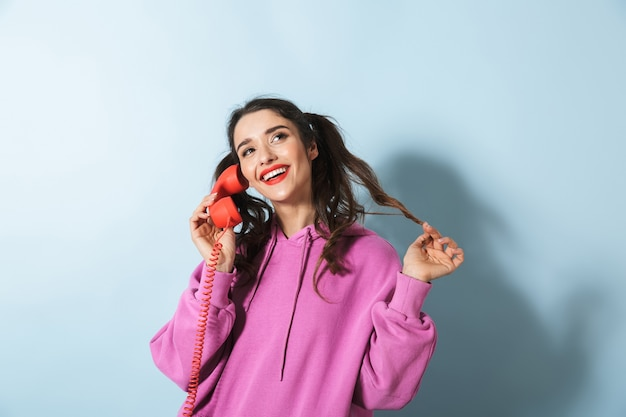 Retrato de uma jovem alegre de moletom em pé sobre o azul, segurando um telefone fixo