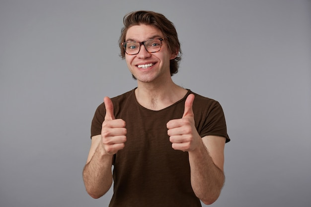 Retrato de uma jovem alegre de óculos, fica sobre um fundo cinza com expressão de surpresa, mostra como gesto e amplamente sorri.