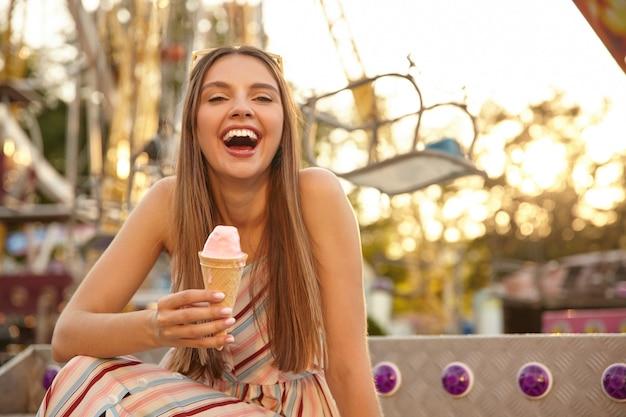 Retrato de uma jovem alegre e adorável com óculos de sol na cabeça posando ao ar livre sobre o parque de atrações, rindo com a boca escancarada e mantendo a casquinha de sorvete na mão