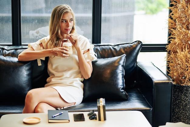 Retrato de uma jovem alegre e bonita bebendo café gelado e olhando para longe