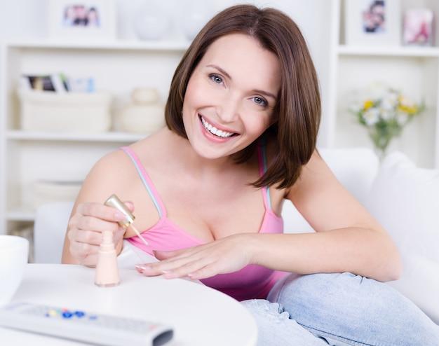 Retrato de uma jovem alegre e feliz linda mulher pintando as unhas