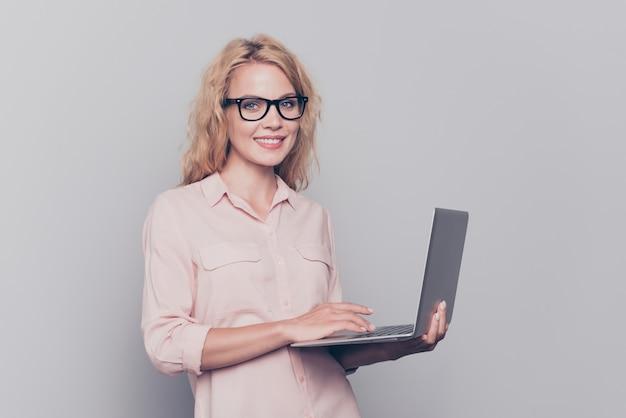 Retrato de uma jovem alegre e inteligente com roupa formal segurando um laptop