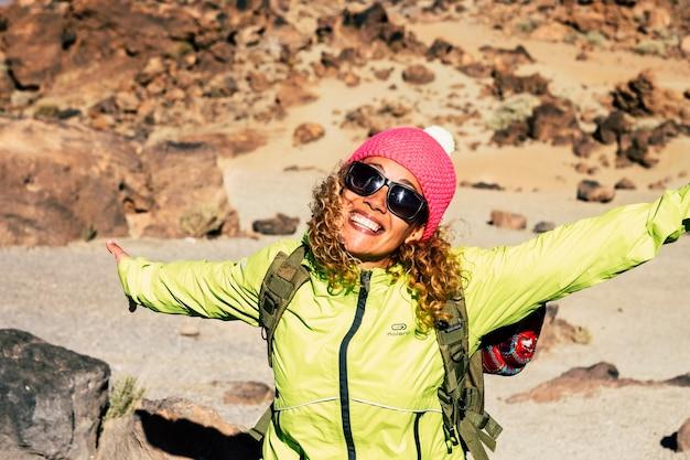 Retrato de uma jovem alegre em óculos de sol em pé com os braços estendidos. mulher desfrutando de caminhadas durante as férias. caminhante despreocupada se divertindo ao ar livre