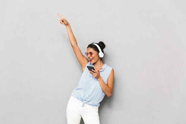 Retrato de uma jovem alegre em óculos de sol, isolado, segurando o telefone celular, ouvindo música com fones de ouvido