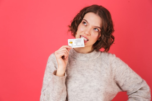 Retrato de uma jovem alegre em pé isolado sobre a rosa, apresentando um cartão de crédito de plástico