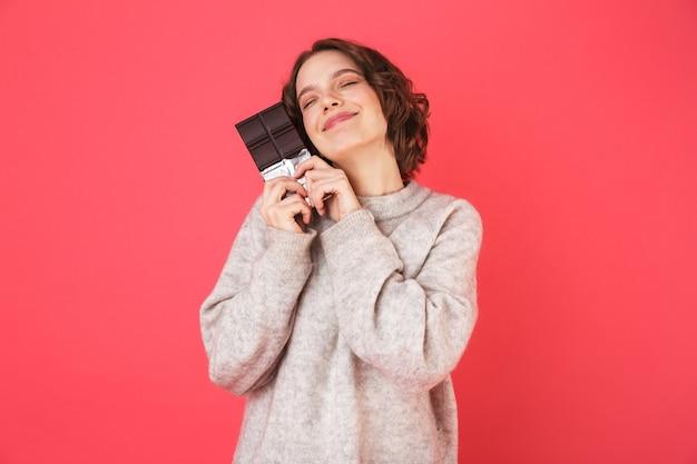 Retrato de uma jovem alegre em pé, isolado sobre a rosa, segurando uma placa de chocolate