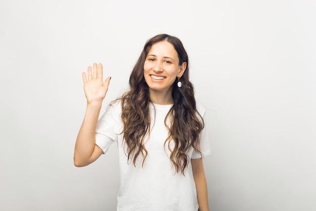 Retrato de uma jovem alegre em uma camiseta branca fazendo um gesto de olá
