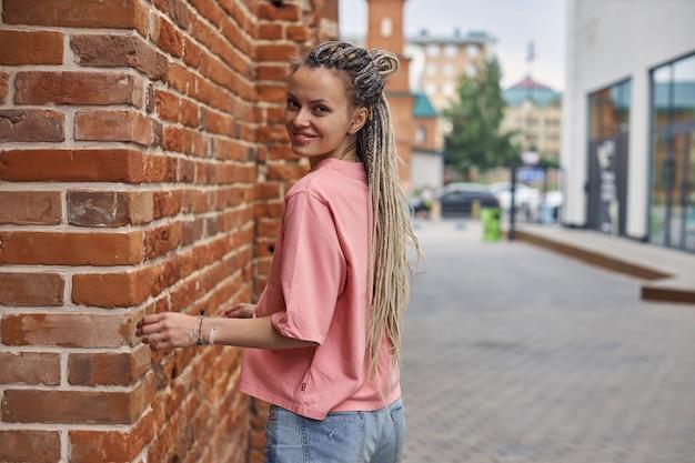 Retrato de uma jovem alegre em uma camiseta rosa no contexto de uma rua de cidade anda ar ...