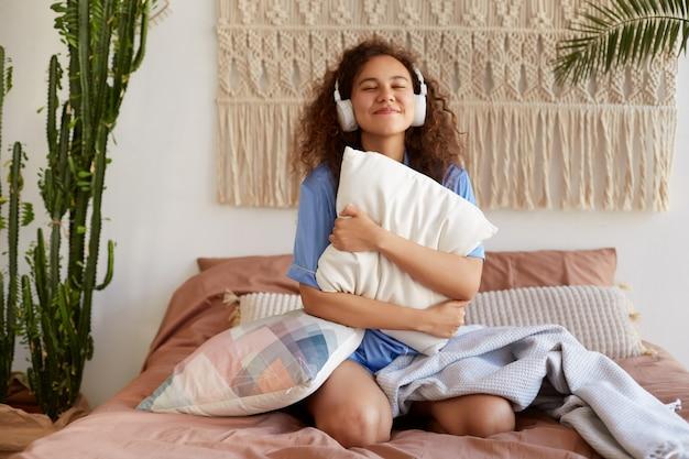 Retrato de uma jovem alegre encaracolada afro-americana, sentada na cama, abraçando um travesseiro, ouvindo música favorita em fones de ouvido, sorrindo com os olhos fechados.