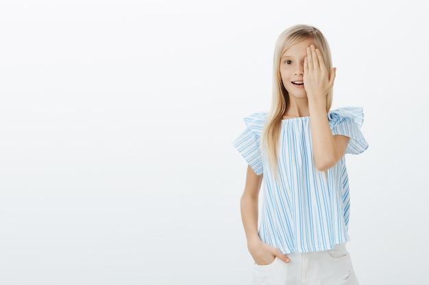 Retrato de uma jovem alegre espantada com cabelos loiros em uma blusa azul, cobrindo metade do rosto e ofegando de surpresa, sendo atordoada com a imagem incrível, em pé sobre uma parede cinza
