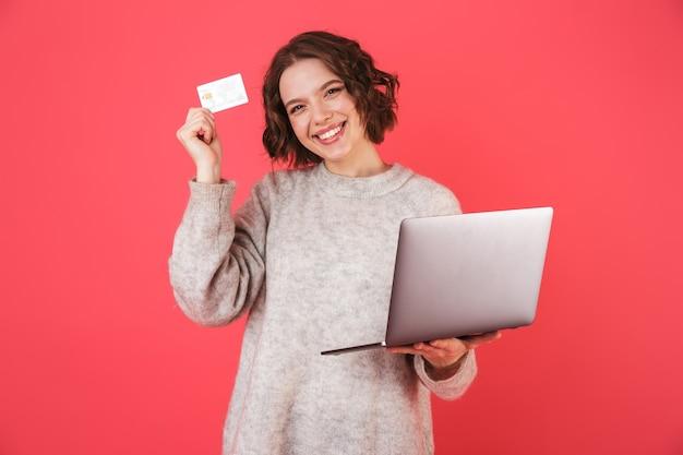 Retrato de uma jovem alegre isolada sobre a rosa, segurando o laptop e mostrando o cartão de crédito