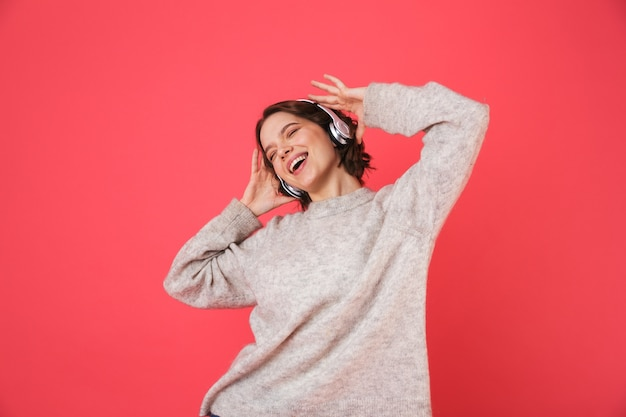 Retrato de uma jovem alegre isolada sobre rosa, ouvindo música com fones de ouvido, dançando