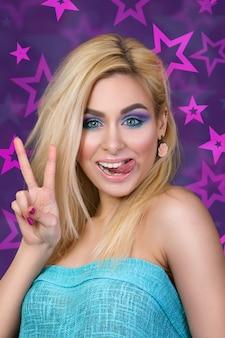 Retrato de uma jovem alegre loira mostrando a língua e o sinal da vitória
