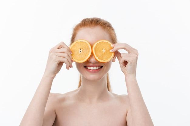 Retrato de uma jovem alegre, segurando duas fatias de uma laranja no rosto, sobre fundo branco da parede