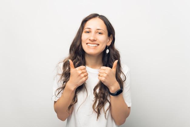 Retrato de uma jovem alegre sorridente em uma camiseta branca mostrando um gesto de polegar para cima
