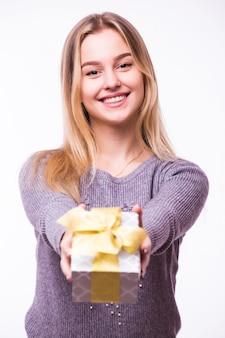 Retrato de uma jovem alegre vestida com um vestido vermelho, segurando uma pilha de caixas de presente e comemorando isolado sobre uma parede branca