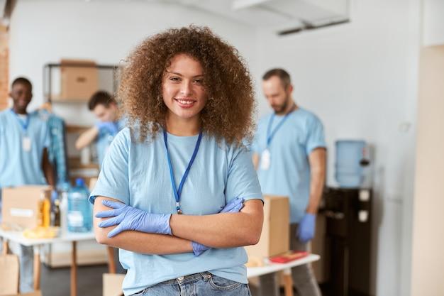 Retrato de uma jovem alegre voluntária em uniforme azul sorrindo para a câmera em pé