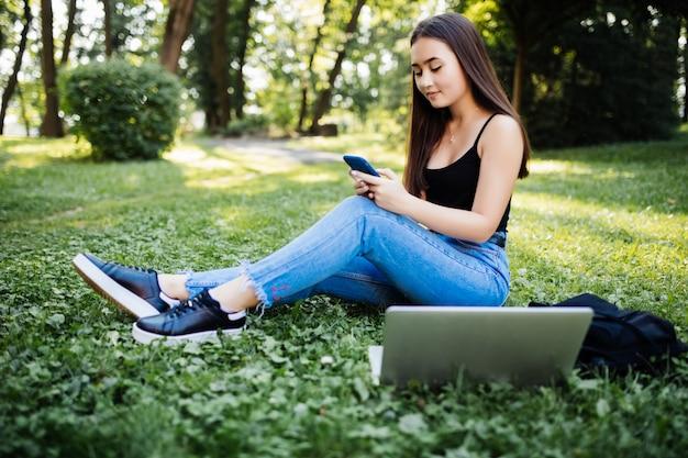 Retrato de uma jovem aluna asiática falando no telefone móvel, olhando para a tela do laptop, ao ar livre