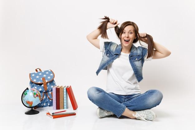 Retrato de uma jovem aluna louca e espantada em roupas jeans, segurando um rabo de cavalo, sentada perto de um globo, uma mochila, livros escolares isolados na parede branca