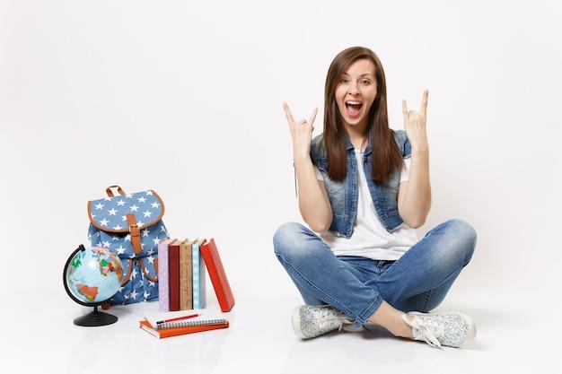 Retrato de uma jovem aluna louca e radiante mostrando uma placa de rock-n-roll sentada perto do globo, mochila, livros escolares isolados na parede branca