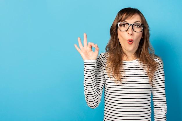 Retrato de uma jovem amigável com um rosto surpreso em uma camiseta casual e óculos faz um gesto bem na luz. rosto emocional. gesto é certo, tudo bem