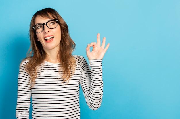 Retrato de uma jovem amigável com um sorriso em uma camiseta casual e óculos faz um gesto bem e olha para cima em azul. rosto emocional. gesto é certo, tudo bem