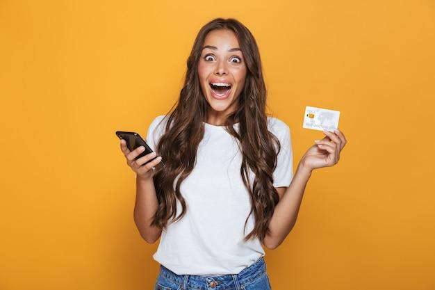 Retrato de uma jovem animada com longos cabelos castanhos em pé sobre uma parede amarela, segurando um telefone celular, mostrando um cartão de crédito de plástico