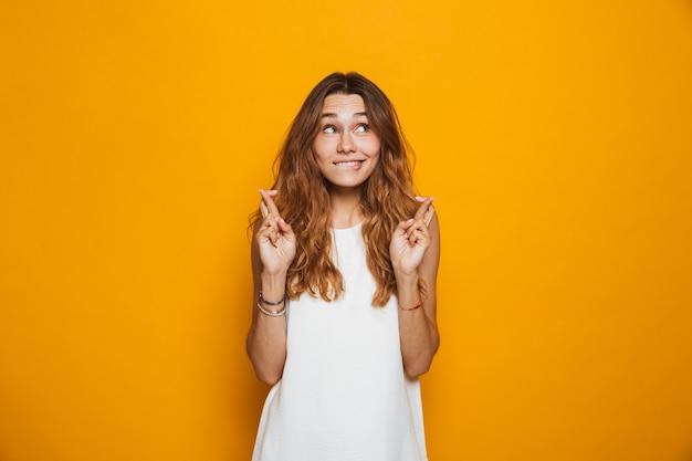 Retrato de uma jovem animada com os dedos cruzados