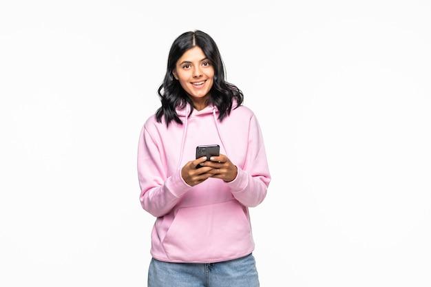 Retrato de uma jovem animada segurando um celular com um capuz isolado na parede branca