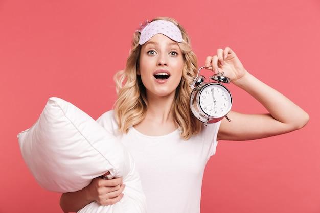 Retrato de uma jovem animada usando máscara para dormir, segurando o despertador e o travesseiro isolados sobre a parede vermelha
