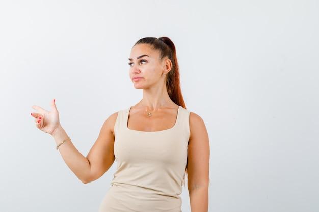 Retrato de uma jovem apontando para o lado em um top e com uma visão frontal confiante