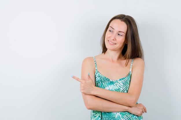 Retrato de uma jovem apontando para o lado esquerdo com a blusa e olhando de frente com alegria