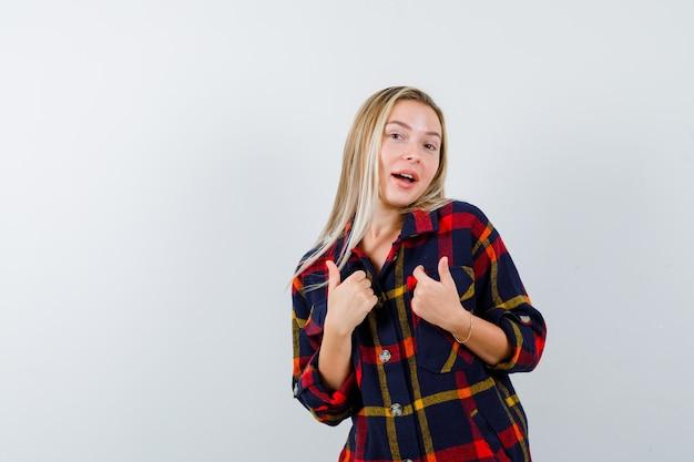Retrato de uma jovem apontando para si mesma em uma camisa quadriculada e com uma vista frontal orgulhosa
