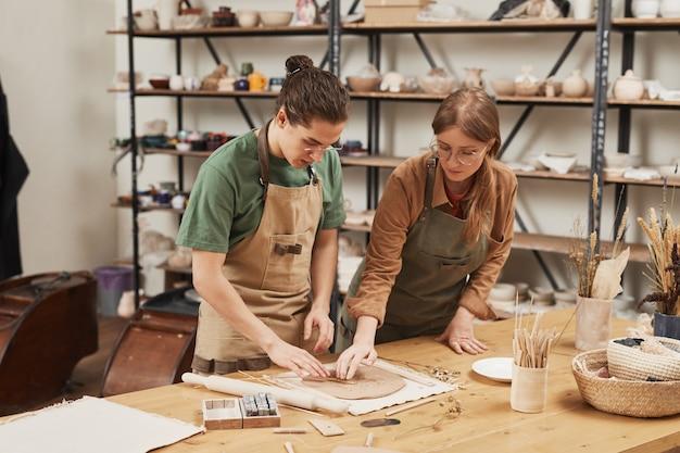 Retrato de uma jovem aprendiz de fabricação de cerâmica na oficina de cerâmica, cópia espaço