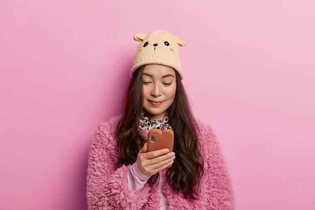 Retrato de uma jovem asain concentrada segurando um telefone celular moderno, usa o aplicativo para bater papo online e envia meme engraçado para um amigo
