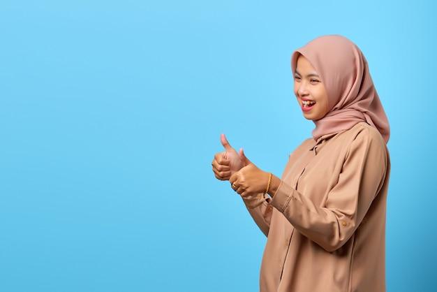 Retrato de uma jovem asiática alegre e animada mostrando os polegares para cima ou um sinal de aprovação para o espaço vazio